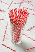Closeup of a glass filled with red and white striped drinking straws. More paper straws are scattered on the rustic white wood table. Vertical format.