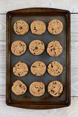 High angle shot of a dozen chocolate chip cookies on a metal baking sheet. Vertical format on a rustic white kitchen table.
