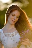 image of red hair  - Long red hair woman in romantic sunset meadow holding bunch of flowers - JPG