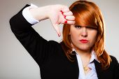 foto of disapproval  - Unhappy business woman giving thumb down gesture looking with negative expression and disapproval on gray - JPG