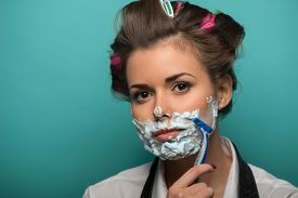 foto of razor  - Cute brunette woman in hair curlers posing with foam on face shaving with razor - JPG