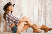 picture of cowgirls  - Beautiful young cowgirl wearing hat and looking at camera while sitting against thewooden background - JPG