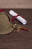 stock photo of private investigator  - Wrapped paper sheets and magnifying glass on Old Wooden table - JPG