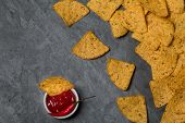 pic of nachos  - Nachos with hot salsa sauce and a red hot chili pepper on a black slate surface top view - JPG