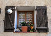 picture of stone house  - French rustic window with old wood shutters and flower pot in stone rural house - JPG