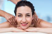 stock photo of spa massage  - Smiling brunette getting back massage in a healthy spa - JPG