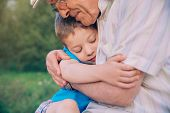 foto of grandfather  - Portrait of happy grandson hugging grandfather over a nature outdoor background - JPG