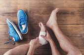pic of ankle shoes  - Unrecognizable injured runner sitting on a wooden floor background - JPG