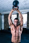 picture of kettles  - Bodybuilder man workout with kettle ball in gym - JPG