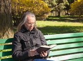 stock photo of sitting a bench  - haired elderly man in a black jacket and glasses reading a book sitting on a bench in city park on sunny spring day - JPG