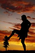 image of cave woman  - A silhouette of a cave woman with her foot on a tree - JPG