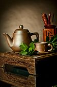 stock photo of loam  - vertical photo still life of the clay teapot and cup on brown background - JPG