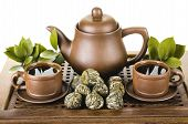 picture of loam  - still life of the clay teapot and cup on wooden trivet on white background isolated - JPG