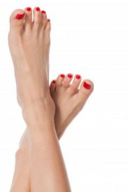 foto of pedicure  - Sexy slender female feet with carefully pedicured fashionable red nails displayed in the crossed position on white with copyspace - JPG