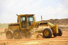 stock photo of power-shovel  - Grader clearing a construction site for a new road - JPG