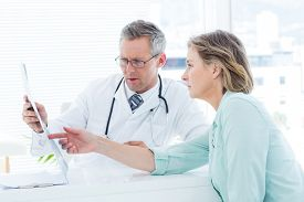 stock photo of mature adult  - Doctor having conversation with his patient and holding xray in medical office - JPG