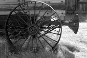Black And White Image Of An Old Weathered Wagon With Rusted Whee poster