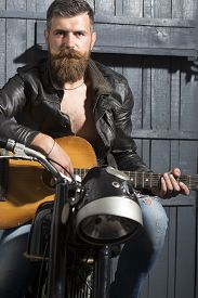 stock photo of moustache  - Attractive young musical man with beard and handlebar moustache in leather jacket sitting on motorcycle with acoustic guitar in garage on wooden wall background vertical picture - JPG