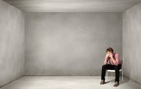 foto of depressed  - Depressed man sitting on a chair all alone - JPG