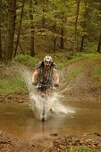 Mountain Biker Splashing Through Stream