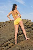 Girl Standing On Rock At Beach