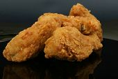 foto of fried chicken  - deep fried fast food spring chicken in golden lemon batter macro close up isolated on black - JPG