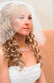 stock photo of low-necked  - Portrait of a young beautiful bride with blonde curly hair in a white low - JPG