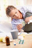 Woman Having Flu Taking Medicines In Bed
