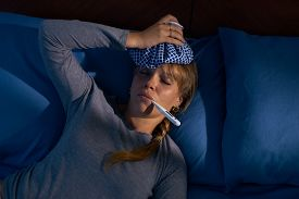 picture of high fever  - Young hispanic woman in pajamas laying on bed with fever and ice bag on head measuring temperature with digital thermometer at night - JPG
