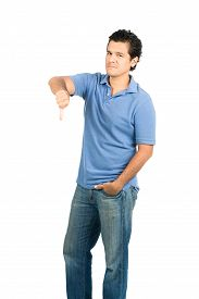 stock photo of disapproval  - Hispanic male looking at camera in blue casual clothes with emotionless facial expression gesturing thumb down showing disapproval disappointment failure negative - JPG