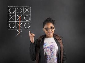 picture of tic  - South African or African American black woman teacher or student with a good idea or answer with tic tac toe thinking out the box diagram standing against a chalk blackboard background inside - JPG
