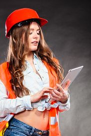 picture of independent woman  - Sexy alluring woman structural engineer wearing helmet holding tablet computer - JPG