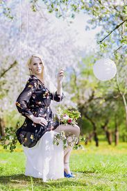 image of seesaw  - Portrait of Sensual Blond Woman Relaxing on Seesaw in Spring Forest - JPG
