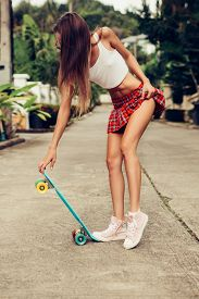 picture of mini-skirt  - Skinny young woman in a sexy red tartan mini skirt and sunglasses hold her blue penny skateboard shortboard while stands on the tropical street - JPG