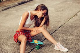 pic of mini-skirt  - Sporty beautiful young woman in a sexy red tartan mini skirt blowing on her broken knee while sitting on her blue skateboard  - JPG