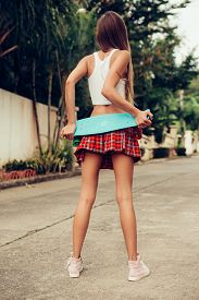 picture of mini-skirt  - Sporty young lady hold her blue penny skateboard shortboard on a sexy red tartan mini skirt while stands on a tropical street - JPG