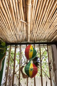 stock photo of reggae  - Hanging wooden spiral decorative craft with reggae color over open window of a tropical hut - JPG