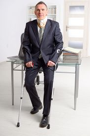 pic of neck brace  - Businessman at work wearing neck brace with crutches - JPG