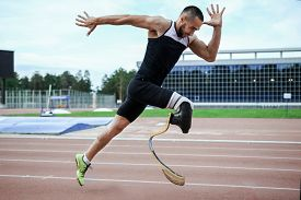 foto of handicapped  - Explosive start of athlete with handicap at the stadium