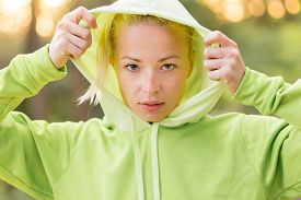 stock photo of hoodie  - Portrait of attractive confident sporty woman wearing fashionable green hoodie while training in the nature - JPG