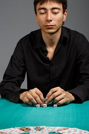 picture of gambler  - Young gambler man in black shirt sitting at the playing table isolated on black background - JPG