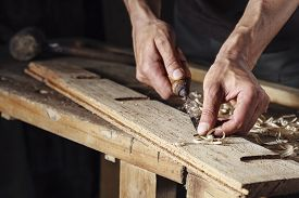 stock photo of chisel  - Closeup of a carpenter hands working with a chisel and carving tools on wooden workbench - JPG