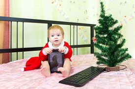 stock photo of new years baby  - Pleased baby in new year suit with tablet computer - JPG
