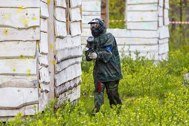 stock photo of paintball  - Young girl playing paintball outdoors in summer - JPG