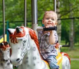 foto of carousel horse  - Smiling child riding a toy horse carousel - JPG