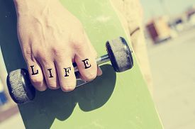 picture of swagger  - closeup of a young man with the word life tattooed in his knuckles holding a skateboard - JPG