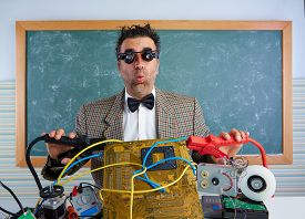 picture of nerds  - Nerd electronics technician retro teacher silly expression with big battery clamps in pcb - JPG