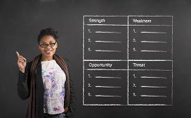 stock photo of swot analysis  - South African or African American black woman teacher or student with a good idea about a SWOT analysis standing against a chalk blackboard background inside - JPG