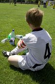 exausted boy takes a rest in the halftime of a football match