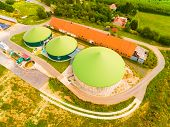 Aerial view over biogas plant and farm in green fields. Renewable energy from biomass. Modern agricu poster